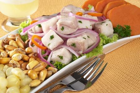 s��kartoffel: Peruanisch-Stil Ceviche gemacht von raw Dornhai (Spanisch: Tollo), roten Zwiebeln und Aji (peruanische Paprika) und serviert mit Mais, Ger�steter Mais (Cancha) und S��kartoffel mit Pisco Sour (peruanischen traditionellen Cocktail) in den R�cken (geringe Tiefensch�rfe, Fokus auf t
