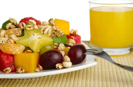 Tropical fruit salad with puffed wheat cereal on table mat with orange juice in the background (Selective Focus, Isolated)   photo