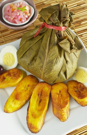 typical: Traditional Peruvian food called Juane from the jungle area. It is a rice dish with meat and eggs covered by bijao leaves and served with fried plantains, eggs and olives (Selective Focus, Focus on the juane) Stock Photo