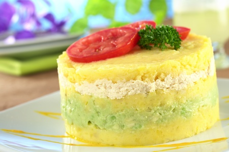 Peruvian dish called Causa made out of mashed potato mixed with lime juice and aji (hot pepper) and filled with avocado and chicken and garnished with tomato slices and parsley (Selective Focus, Focus on the front)