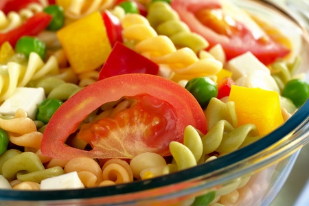 Pasta salad with fresh vegetables (tomato, pea, bell pepper, cucumber) in glass bowl (Selective Focus, Focus on the tomato slice)  photo