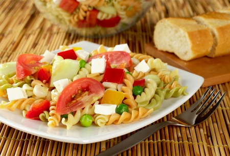 Pasta salad with fresh vegetables (tomato, pea, bell pepper, cucumber) and cheese on plate with fork next to it and baguette in the back (Selective Focus, Focus on the front of the salad)  Stock Photo - 9142650