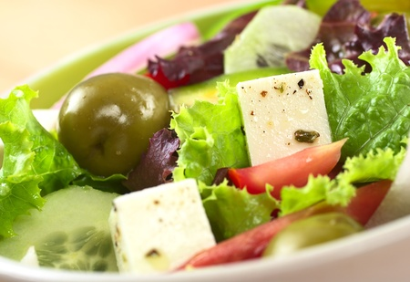 Greek salad out of cheese, green olives, tomato, green bell pepper, red onion, cucumber and lettuce (Selective Focus, Focus on the cheese on the right)  photo