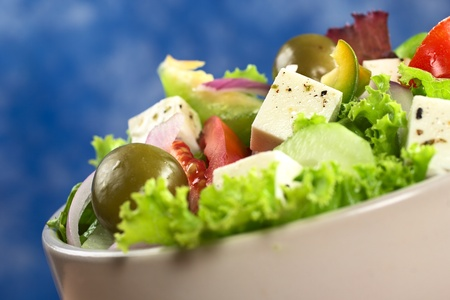 Greek salad out of cheese, green olives, tomato, green bell pepper, red onion, cucumber and lettuce with blue background (Selective Focus, Focus on the cheese in the middle)  photo