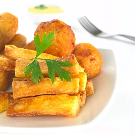cassava: Fried manioc sticks garnished with parsley with fork and dip in the back (Selective Focus, Focus on the sticks and the parsley) Stock Photo