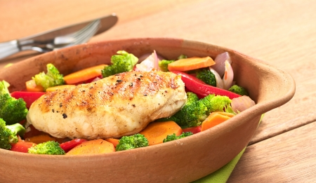 Fried chicken breast with pepper on top surrounded by vegetables (onion, carrot, broccoli, red bell pepper) (Selective Focus, Focus on the front of the meat) photo