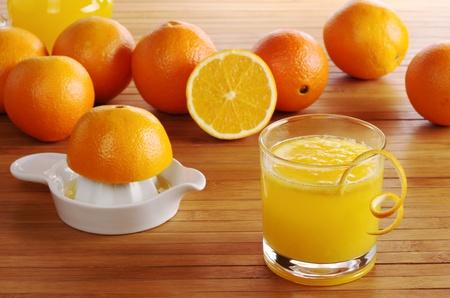 juice squeezer: Fresh orange juice with orange juice squeezer and oranges on wooden mat (Selective Focus) Stock Photo