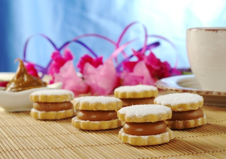 Peruvian cookies called Alfajor on tablemat with coffee and pink flowers in the background (Selective Focus) photo