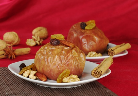 Baked apple with walnuts, raisins, almonds and cinnamon on brown table mat and red fabric as background (Selective Focus)  photo