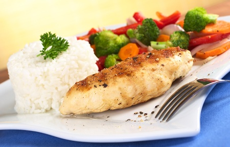 chicken breast: Chicken breast with pepper on top, vegetables (carrot, broccoli, onion, red bell pepper) and rice garnished with parsley (Selective Focus, Focus on the front of the meat)