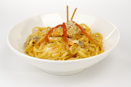 Fettuccine with chicken, mushrooms and red pepper garnished with sticks on white (Selective Focus)  photo