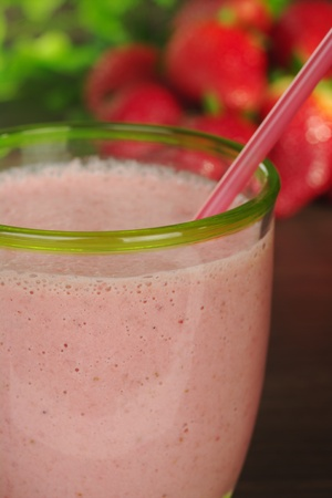 Strawberry milkshake with drinking straw and strawberries in the background (Selective Focus, Focus on front rim of the glass)