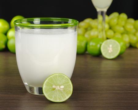 Pisco Sour, un cóctel peruano de licor de uva, jarabe de azúcar, el jugo de limón y el huevo (enfoque selectivo, centrarse en la llanta delantera del vidrio y la mitad de una CAL)  Foto de archivo - 9193121