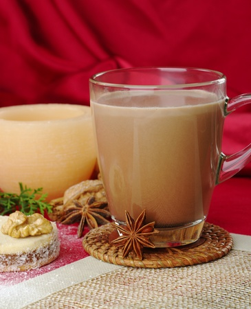 alfajor: Hot chocolate in glass cup with anise, cookie, and candle in the background (Selective Focus, Focus on the glass cup) Stock Photo