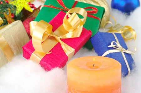 Lit orange candle and colorful presents with christmas decoration on cotton (Selective Focus, Focus on candle) Stock Photo - 9193111