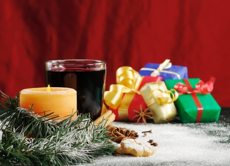 Lit candle with cookies, powder sugar, mulled wine and colorful gifts in the background (Selective Focus, Focus on candle) photo