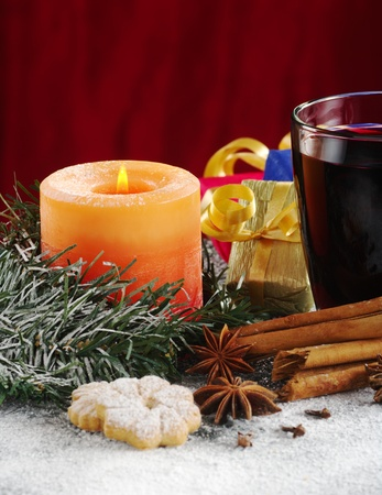 Candle and mulled wine with cookies, spices and Christmas gifts (Selective Focus, Focus on the candle and the mulled wine) photo
