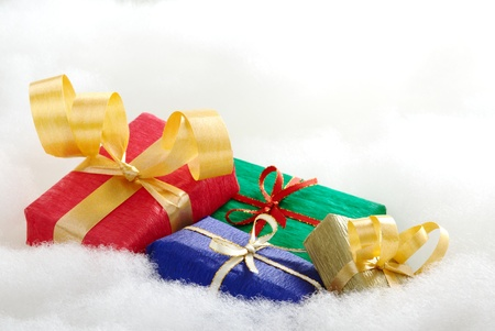 Colorful Christmas gifts on white cotton that looks like clouds (Selective Focus, Focus on the blue and golden gift boxes) Stock Photo - 9193238
