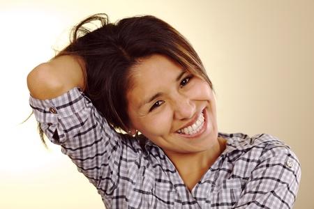 peruvian ethnicity: Hermosa joven peruana riendo y sosteniendo su cabello en la espalda con una mano (enfoque selectivo, centrarse en los ojos)