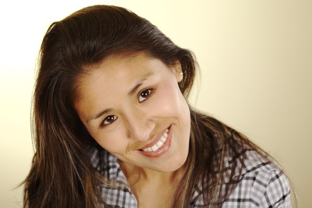 peruvian ethnicity: Beautiful young Peruvian woman with long brown hair smiling and looking up into the camera (Selective Focus, Focus on the eyes)