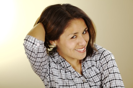 peruvian ethnicity: Hermosa joven peruana sonriente y sosteniendo su cabello en la espalda con una mano y buscar en la c�mara (enfoque selectivo, centrarse en los ojos)
