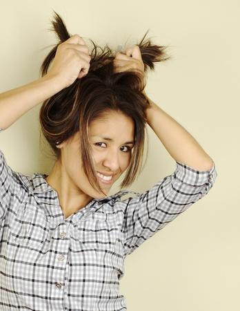 peruvian ethnicity: Hermosa joven peruana sonriente y sosteniendo su cabello en la parte de atr�s con dos manos y mirando hacia la c�mara (enfoque selectivo, centrarse en los ojos)