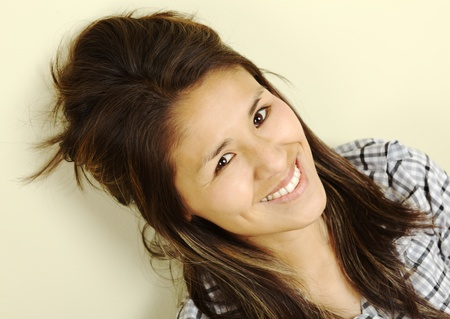 peruvian ethnicity: Beautiful young Peruvian woman with long brown hair smiling and leaning against a wall looking up into the camera (Selective Focus, Focus on the eyes)