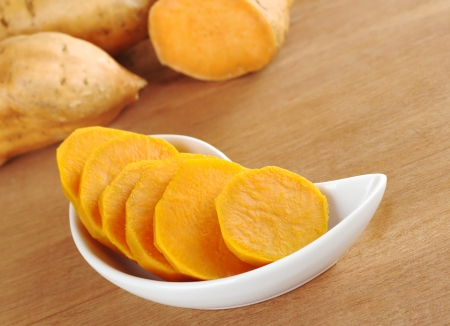 tuberous: Cooked sweet potato (lat. Ipomoea batatas) cut in slices in white bowl on wooden surface with sweet potatoes in the background (Selective Focus, Focus on the sweet potato in the bowl)