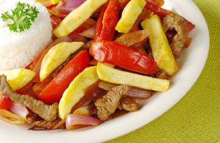 Un piatto tipico peruviano chiamato Lomo Saltado che è fatto di carne di manzo, cipolle, pomodori ed è accompagnato da patate fritte e riso (Focus selettiva, Focus sulla parte anteriore del piatto) Archivio Fotografico - 9193279