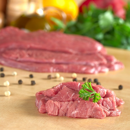 Fresh raw beef meat with parsley on top, with vegetables, herbs and kitchen utensils in the back (Selective Focus, Focus on the front of the meat and the parsley) photo