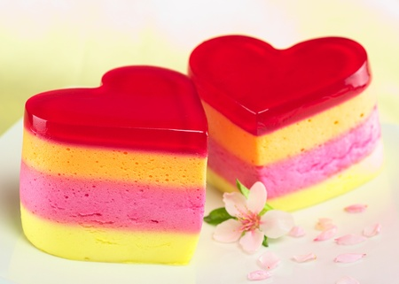 Colorful Peruvian heart-shaped jelly-pudding cakes called Torta Helada with a peach blossom on the plate (Selective Focus, Focus on the three upper lines on the front of the left cake) photo