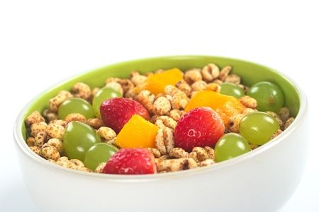 Fresh and healthy breakfast: Fruit salad out of mango, strawberry and white grape with puffed wheat cereal (Selective Focus, Focus on the middle of the bowl) Stock Photo - 9258681