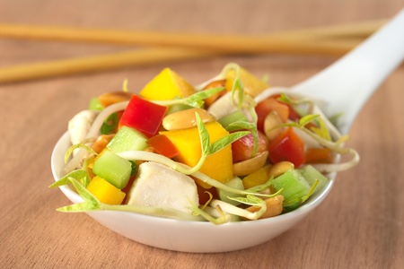 Fresh Asian salad with chicken, mango, cucumber, bean sprouts, red bell pepper and peanuts on white ceramic spoon with wooden chopsticks in the back (Selective Focus, Focus on the front of the food) photo