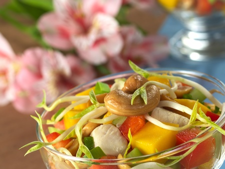 bean sprouts: Fresh Asian salad with chicken, mango, cucumber, bean sprouts, red bell pepper and peanuts in glass bowl with inca lily in the back (Selective Focus, Focus on the cashew nut and the bean sprout on the top)