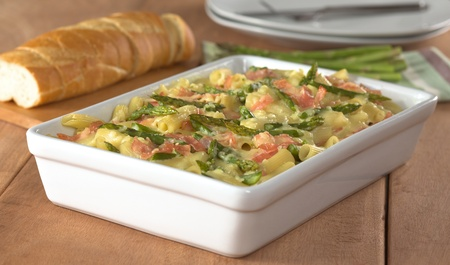 Casserole of green asparagus, ham and macaroni with baguette slices and plates in the back (Selective Focus, Focus in the middle of the dish) Stock Photo - 9301161