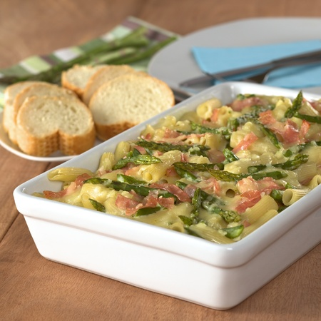 Casserole of green asparagus, ham and macaroni with baguette slices and plates in the back (Selective Focus, Focus in the middle of the dish) photo