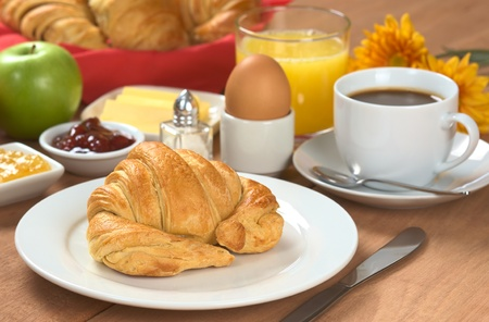 continental breakfast: Delicious continental breakfast consisting of coffee, orange juice, croissant, boiled egg, jam, butter and apple (Selective Focus, Focus on the front of the croissant) Stock Photo