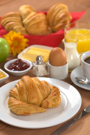 continental breakfast: Delicious continental breakfast consisting of coffee, milk, orange juice, croissant, boiled egg, jam, butter and apple (Selective Focus, Focus on the front of the croissant) Stock Photo