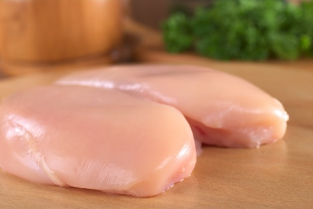 Raw chicken breast with wooden mortar and fresh parsley in the back (Selective Focus, Focus on the front of the meat) Stock Photo - 9365584