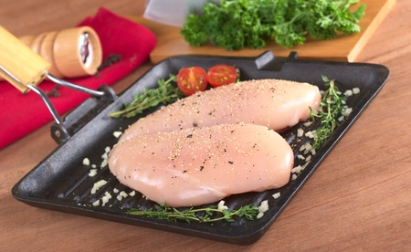 Raw chicken breast in frying pan seasoned with pepper, garlic and thyme with fresh herb as well as a pepper mill in the back (Selective Focus, Focus on the front of the meat) photo