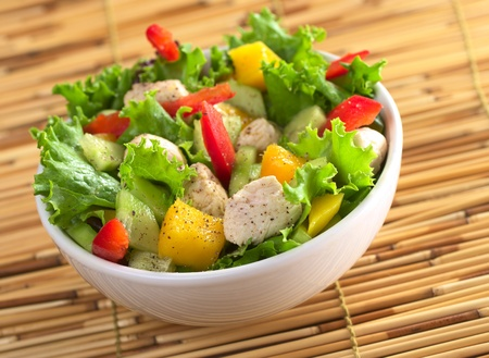 Fresh chicken salad seasoned with pepper with lettuce, mango, red bell pepper and cucumber (Selective Focus, Focus on the salad in the front)