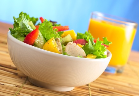 Fresh and healthy chicken salad with lettuce, mango, red bell pepper and cucumber with fresh juice in the back in front of blue background (Selective Focus, Focus on the front of the salad) photo