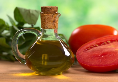 Olive oil with tomato and basil leaves in the back (Selective Focus, Focus on the front of the bottleneck and the handle) Stock Photo