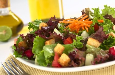Fresh salad of lettuce, tomato, cucumber, radish, carrot and croutons (Selective Focus, Focus on the carrot on top) photo
