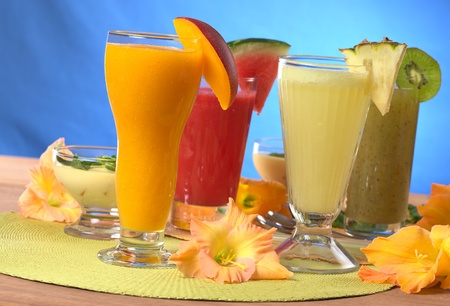 pineapple  glass: Mango, pineapple, watermelon and kiwi smoothies surrounded by gladiolus flower (Selective Focus, Focus on the mango and pineapple smoothies in the front) Stock Photo