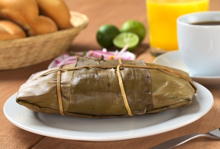 Peruvian food called Tamal which is prepared from cooked corn mixed with chicken meat and wrapped in banana leaves. It is eaten for breakfast or as appetizer at lunchtime (Selective Focus, Focus on the front of the tamal)