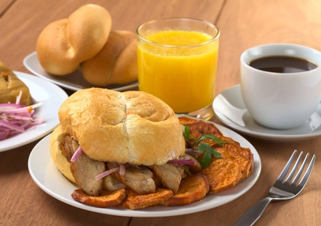 Typical Peruvian breakfast consisting of Pan con Chicharron (Bun with fried meat) and fried sweet potato, tamal (on the left), salsa criolla (onion salad) with coffee, orange juice and buns (Selective Focus, Focus on the front)