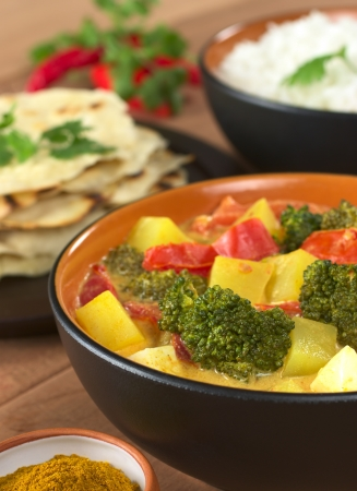 indian meal: Delicious vegetarian Indian curry with rice and chapati flatbread in the back (Selective Focus, Focus on the broccoli in the front)