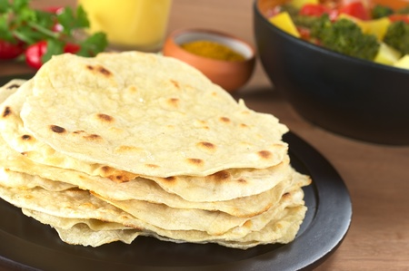 Indian flatbread called Chapati with vegetable curry, curry and mango lassi in the back (Selective Focus, Focus on the front of the chapati)  photo