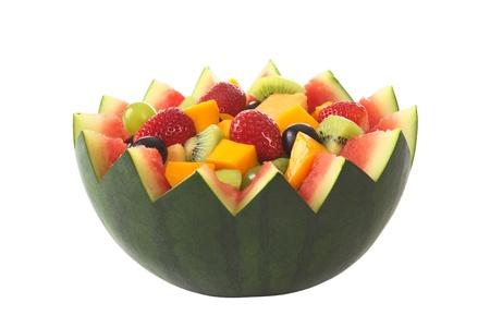 salade de fruits: Salade de fruits frais de mangue, fraise, kiwi et raisins dans un bol d'past�ques isol� sur blanc (s�lective focus, Focus dans le milieu de la salade de fruits) Banque d'images